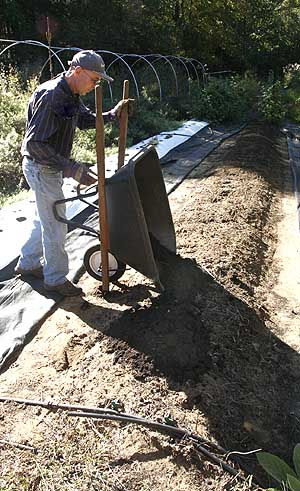 Adding compost to bed row.