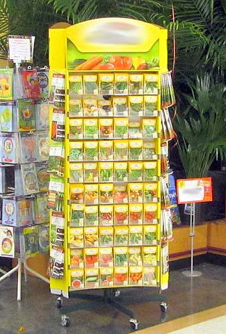 Seed rack in store. In bright light, next to card racks and backed by plants. Humidity will be high near the plants and bright light and heat is not ideal for seed viability.